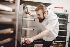 Baker gluurt in de oven en regelt temperatuur van baksel in de bakkerij royalty-vrije stock foto