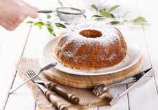 Baker hand dusting Bundt Cake with icing sugar Stock Image