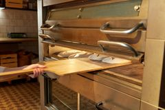 Baker hand putting dough into bread oven at bakery Royalty Free Stock Photos