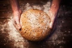 Baker handen met vers brood op lijst royalty-vrije stock afbeeldingen