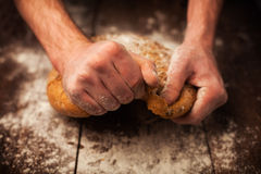 Baker handen met vers brood op lijst stock fotografie