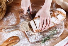 Baker hands cutting bread Royalty Free Stock Photo