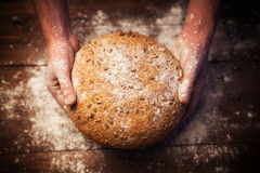 Baker hands with fresh bread on table Royalty Free Stock Images