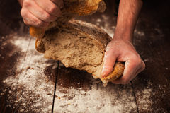 Baker hands with fresh bread on table. Baker hands with fresh bread on wood table Royalty Free Stock Photo