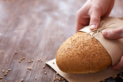 Baker hands with fresh bread on wood table Royalty Free Stock Photography