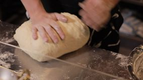 Baker hands knead the dough. In restaurant stock footage