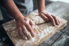 Baker hands kneading the dough with flour Royalty Free Stock Image