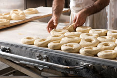 Baker hands making bread donuts. Close-up male baker hands making Italian frisella bread donuts, placing raw dough over bakery table Stock Photography