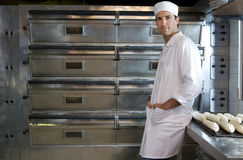 Baker with hands in pockets by baguettes, smiling, portrait Royalty Free Stock Photography