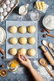 Baker hands preparing dough for buns ingridients food flat lay on kitchen table Royalty Free Stock Photos