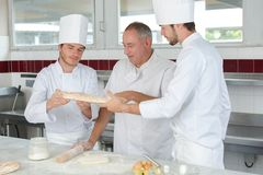 Baker and assistants working in kitchen. Baker and his assistants working in kitchen royalty free stock images