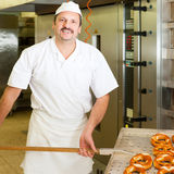 Baker in his bakery baking bread Royalty Free Stock Photo