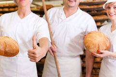 Baker with his team in bakery. Baker standing with his team in bakery with freshly baked bread Royalty Free Stock Photos