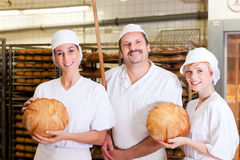 Baker with his team in bakery. Baker standing with his team in bakery with freshly baked bread stock images