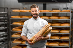 Baker holding baguettes at the manufacturing. Handsome baker in uniform holding baguettes with bread shelves on the background at the manufacturing Royalty Free Stock Photo