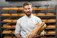 Baker holding baguettes at the manufacturing. Handsome baker in uniform holding baguettes with bread shelves on the background at the manufacturing Stock Images