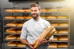 Baker holding baguettes at the manufacturing. Handsome baker in uniform holding baguettes with bread shelves on the background at the manufacturing Stock Image