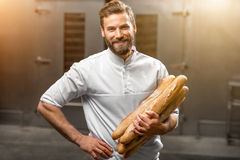 Baker holding baguettes at the manufacturing. Handsome baker in uniform holding baguettes with oven on the background at the manufacturing Stock Photos