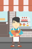 Baker holding basket with bakery products. Royalty Free Stock Image