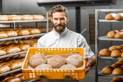 Baker holding breads at the manufacturing Royalty Free Stock Images