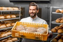 Baker holding breads at the manufacturing. Handsome baker holding box full of freshly baked buckweat breads at the manufacturing stock image