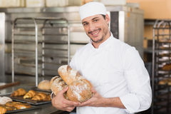 Baker holding freshly baked loaves Royalty Free Stock Images