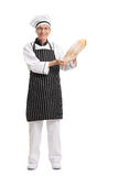 Baker holding a loaf of bread. Full length portrait of a baker holding a loaf of bread isolated on white background stock image