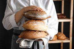 Baker holding loaves of bread indoors. Closeup royalty free stock images