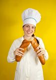 Baker holding long bread rolls Royalty Free Stock Image