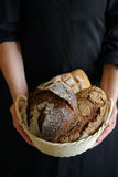 Baker holding rustic breads Royalty Free Stock Images