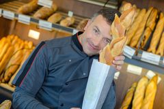 Baker holding up baguette royalty free stock image