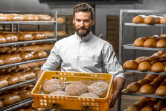 Baker holdingsbroden bij de productie royalty-vrije stock afbeeldingen
