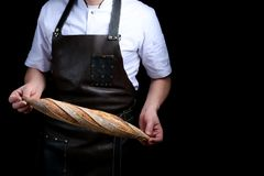 Baker holds baguette isolated on black background stock images