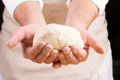 Baker holds raw dough in hands Royalty Free Stock Photos