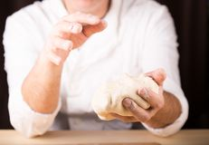 Baker holds raw dough in hands Stock Photos