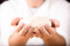 Baker holds raw dough in hands Stock Photography
