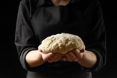 Baker houdt gistdeeg op een zwarte achtergrond met bevroren bloem in de lucht, brood, brioche, croissants, pizza, deegwaren Conce royalty-vrije stock afbeeldingen