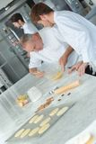 Baker instructing apprentice how to knead dough properly royalty free stock images