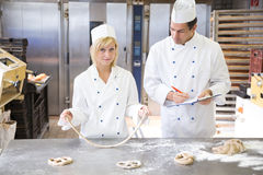 Baker instructs apprentice how to form pretzel Stock Photos