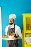 Baker in the kitchen. Happy young baker holding fresh bread on tray Royalty Free Stock Photography