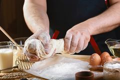 Baker knead dough bread, pizza or pie recipe ingredients with hands, food on kitchen table background, working with milk, yeast, f. Lour, eggs, sugar pastry or royalty free stock image