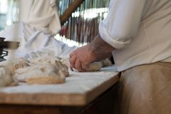 Baker knead the dough on a table. Hands of baker knead the dough on a table Royalty Free Stock Photography