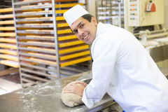 Baker kneading dough in bakery Stock Photography