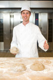Baker kneading dough in bakery or bakehouse Stock Image