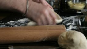 Baker kneading dough in flour on table stock footage