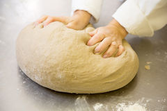 Baker kneading fresh bread dough in bakery Royalty Free Stock Photos