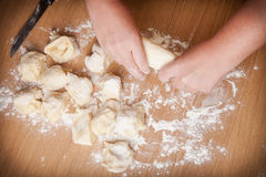 Baker kneads uncooked dough on a wooden table Stock Photos