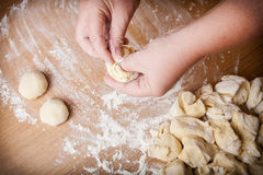 Baker kneads uncooked dough on a wooden table.  Stock Photo