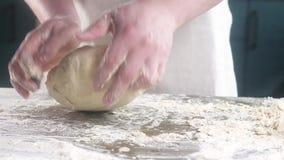 Baker kneedt het deeg voor de pastei Kneedt het deeg op de lijst met vuile handen Close-up Langzame motie stock videobeelden