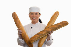 Baker with long rolls. Baker holding a variety of long french sticks stock photos